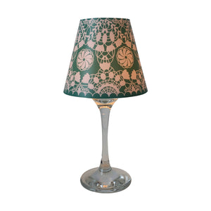 "Wine glass with green ""lamp"" shade with white lace design."