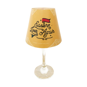 "Wine glass with ""lamp"" shade with Eastern Love Affair Logo on yellow background."