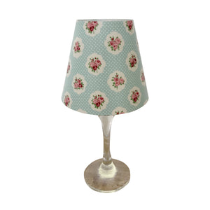 "Wine glass with ""lamp"" shade with small vintage roses pattern on turquoise background."