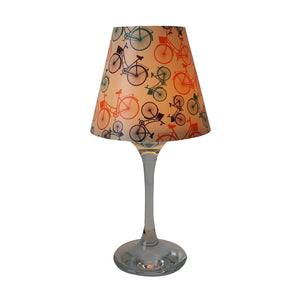 "Wine glass with ""lamp"" shade with colorful bikes pattern on white background."
