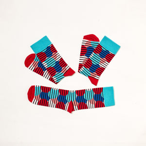 Soseta3 pair of socks with red, dark and light blue circles covered by black thin horizontal stripes. 3 socks in one pair, unfolded.