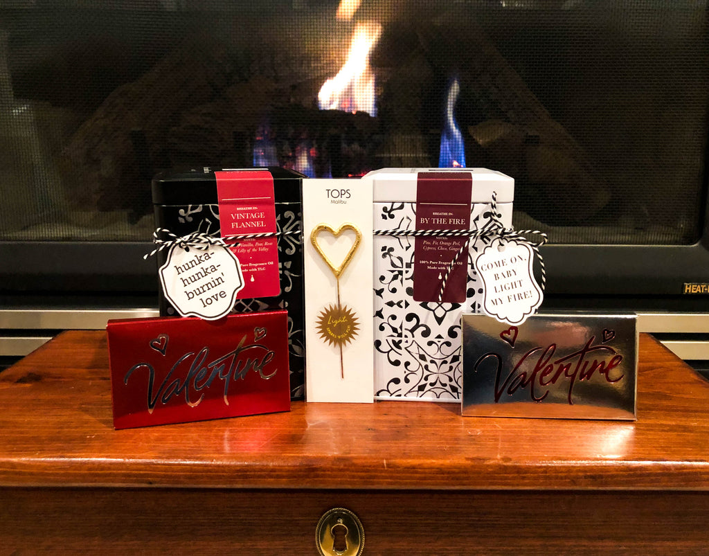 His and Hers luxury candle perched by a fireplace with gourmet Valentine's chocolate bars