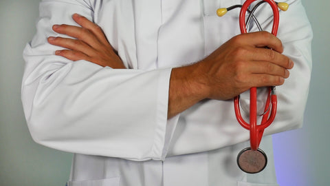 medical professional holding a red stethoscope