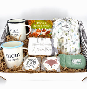 "Adventure-themed baby gift basket curated and personalized. Contains: Engraved camp mugs for Mom and Dad, baby onesie that says, ""I am the Adventure,"" Tree-themed baby swaddle, Adventure awaits baby booties, Babies in the Forest board book and two gourmet cut-out cookies for Mom and Dad. Beautifully packaged and shipped directly to recipient."