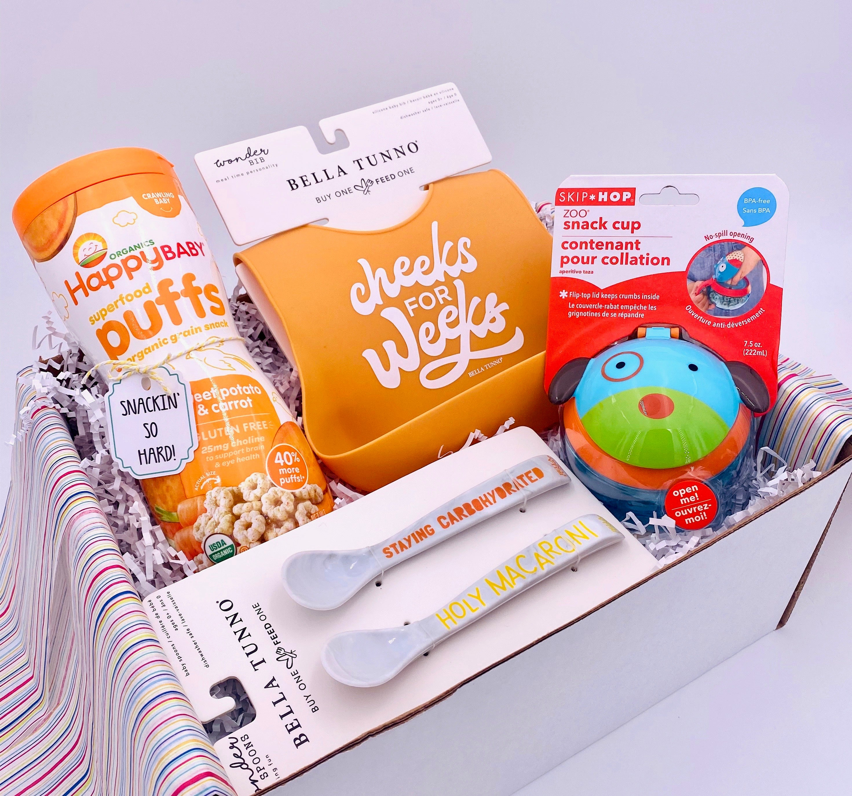 Happy Pak Baby gift basket beautifully arranged in a box. Filled with designer, silicone bib, Doggie-themed, portable snack cup, Designer eating spoons, and Happy Baby Organic snack puffs.