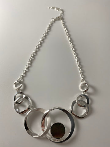 Short necklace, with silver interlinked circular stations and mother of pearl detail.