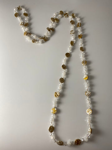 Long necklace, with yellow gold-tone stations and transparent beads.