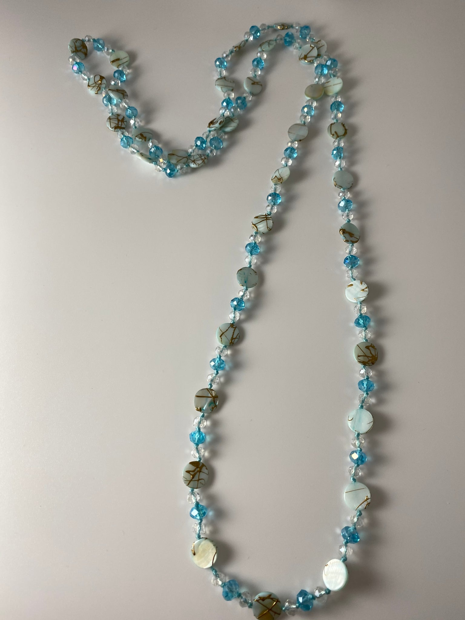 Long necklace, with silver-tone stations and aqua beads.
