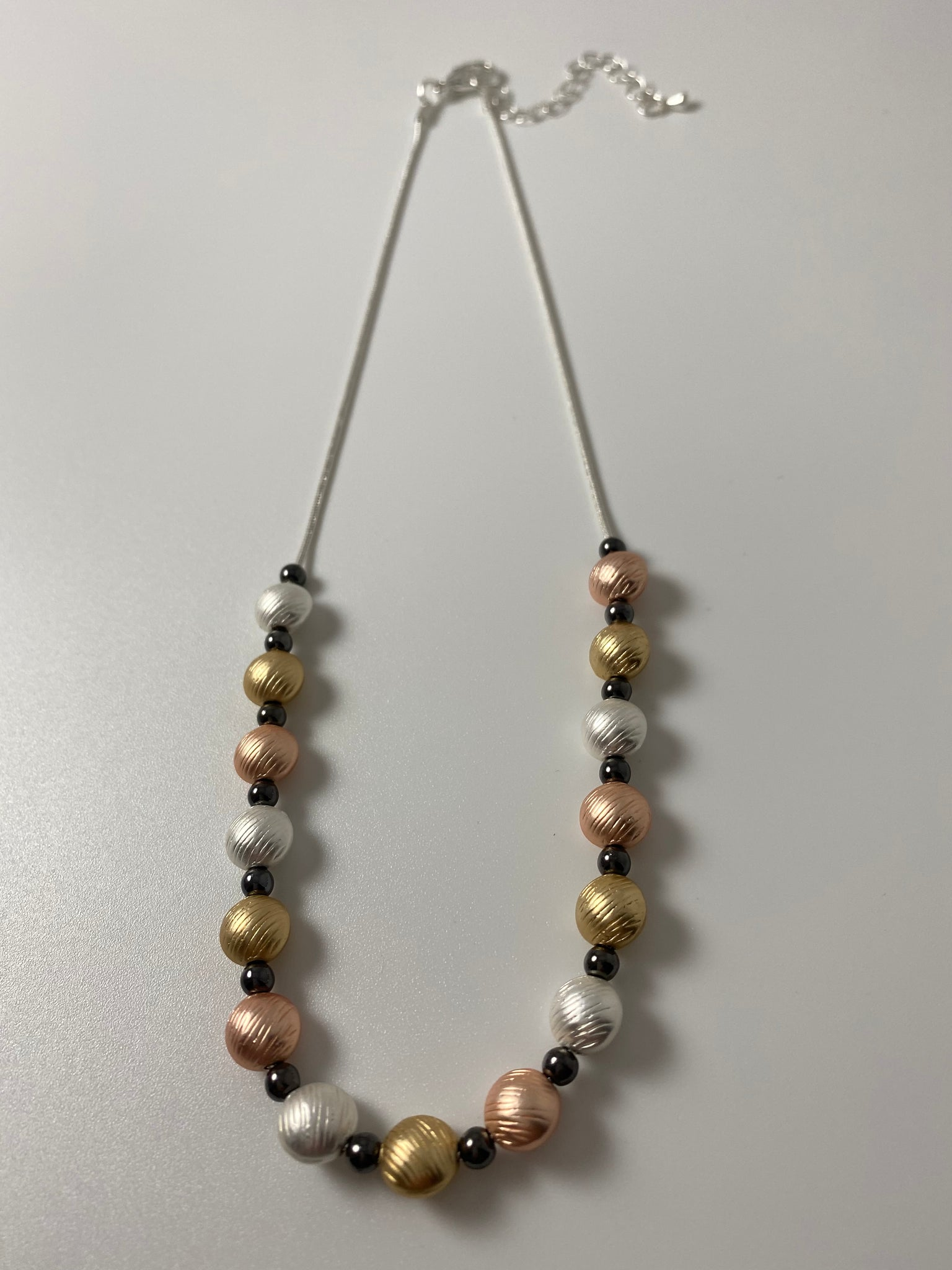Short necklace, with tri-tone circular stations.