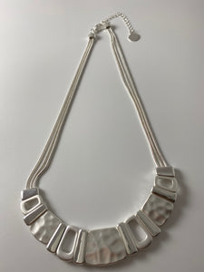 Short necklace, with battered/shiny silver tone bar.