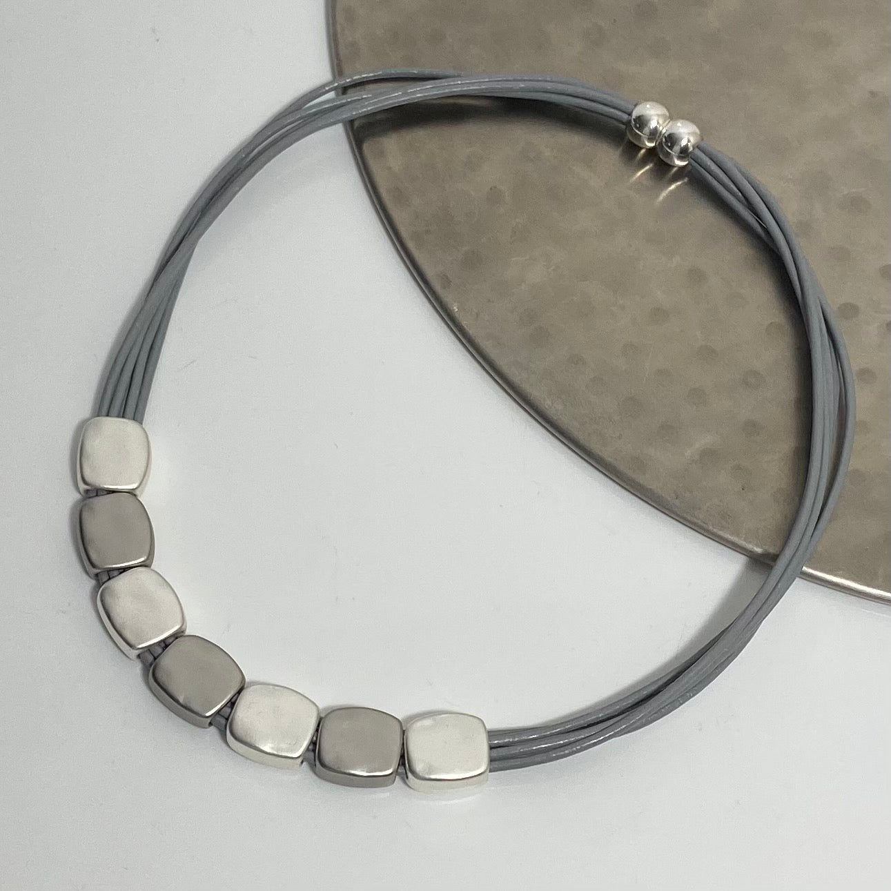 Short necklace, with grey and silver tone nuggets with a magnetic clasp on grey leather strands