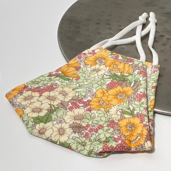 Ditsy orange and green floral print face mask with adjustable earstrings
