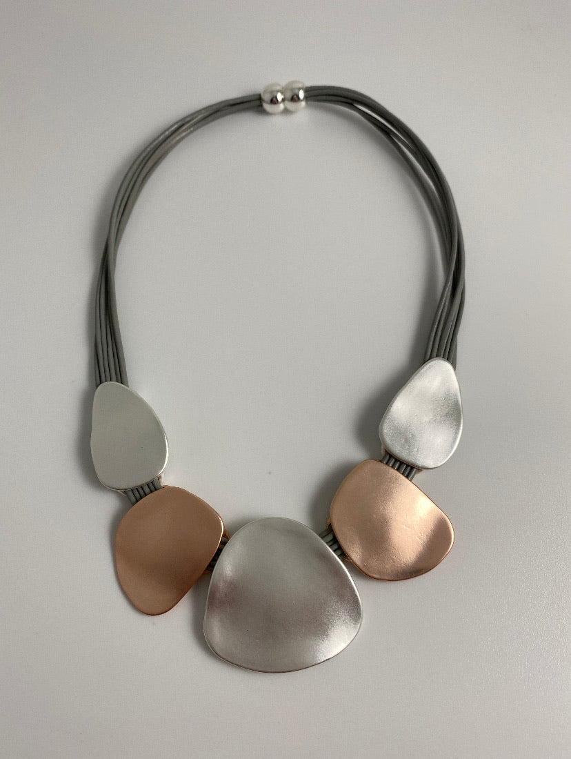 Short necklace, with rose gold and silver tone dented metal, including a magnetic clasp