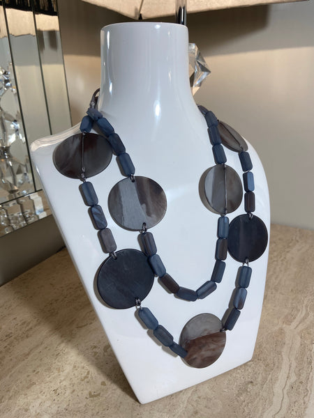 Long necklace, with navy, grey and blue circular stations and grey drawstring to adjust the length
