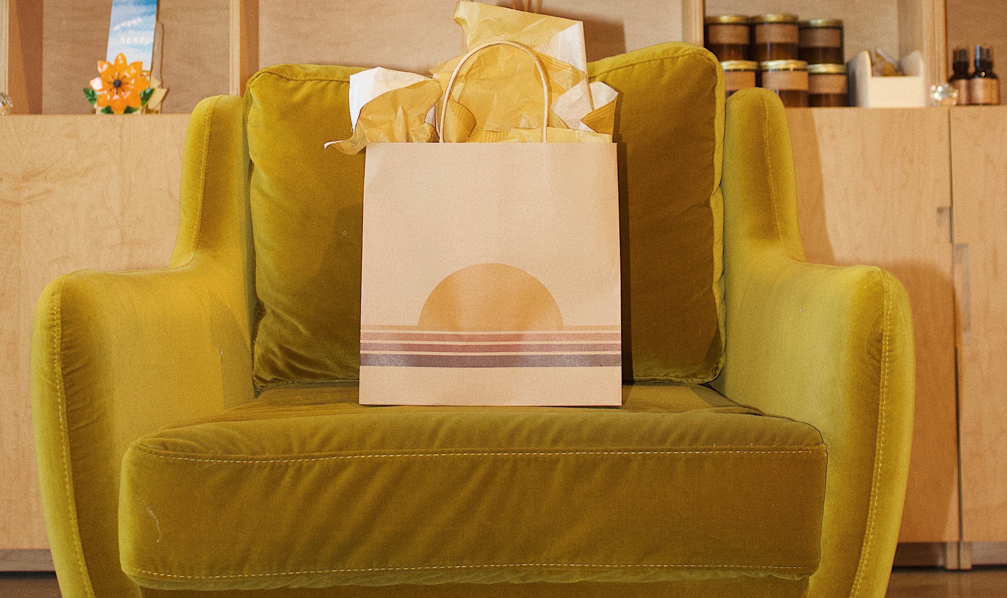 Yellow velvet armchair with P.F. Candle Co. branded gift bag in seat