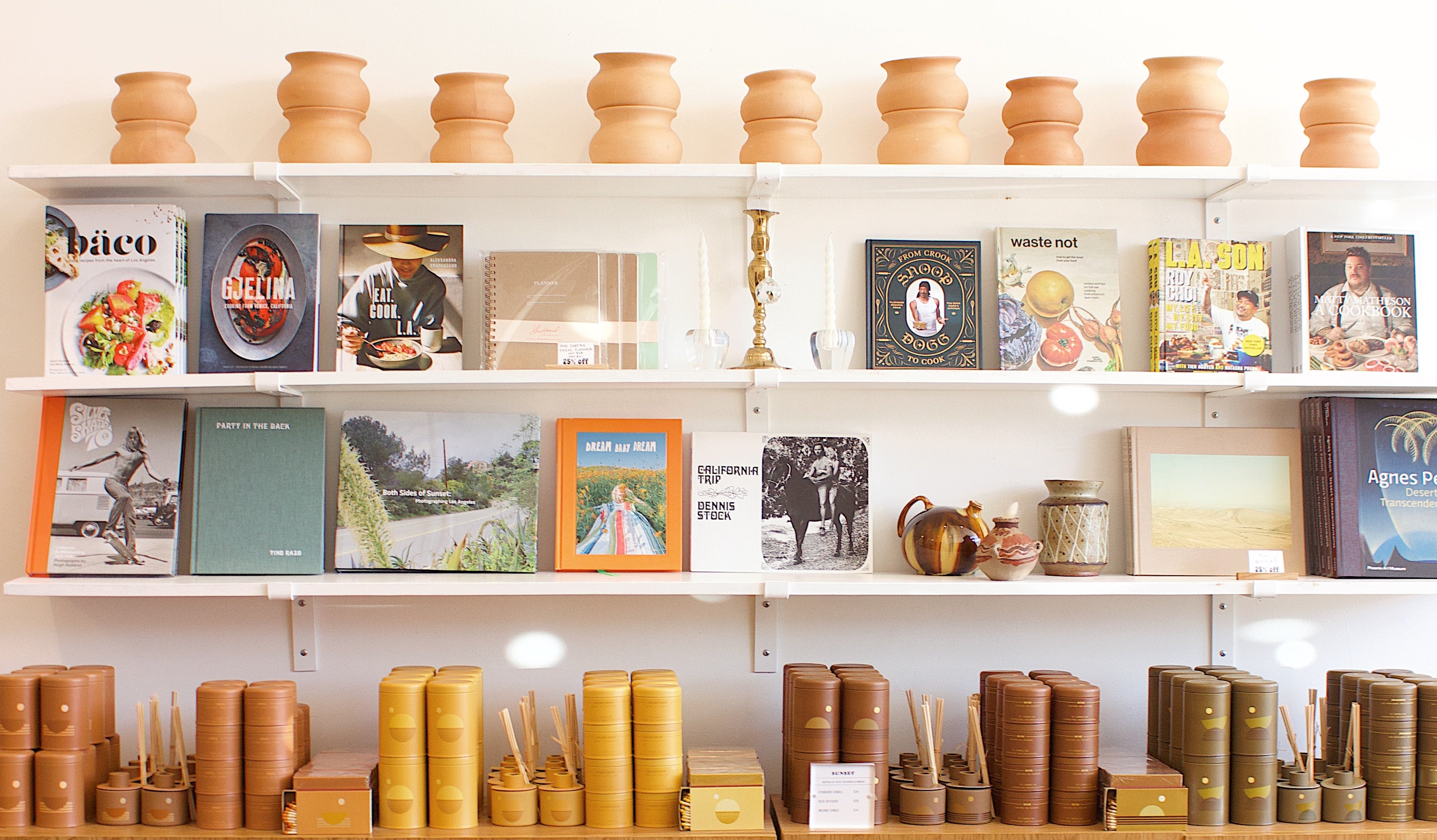 Four white walls shelves display terracotta pots, lifestyle books, and P.F. Candle Co.'s Sunset Line