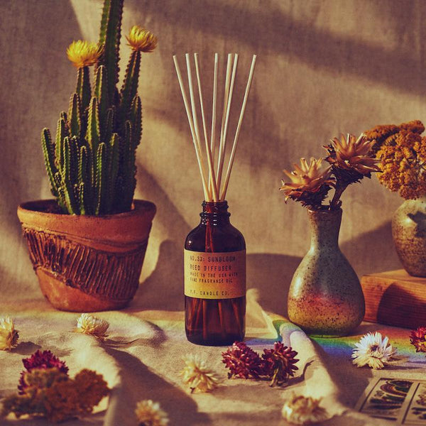 PF Candle Co Sunbloom reed diffuser on a tan table surround by dried flowers with a rainbow shining down