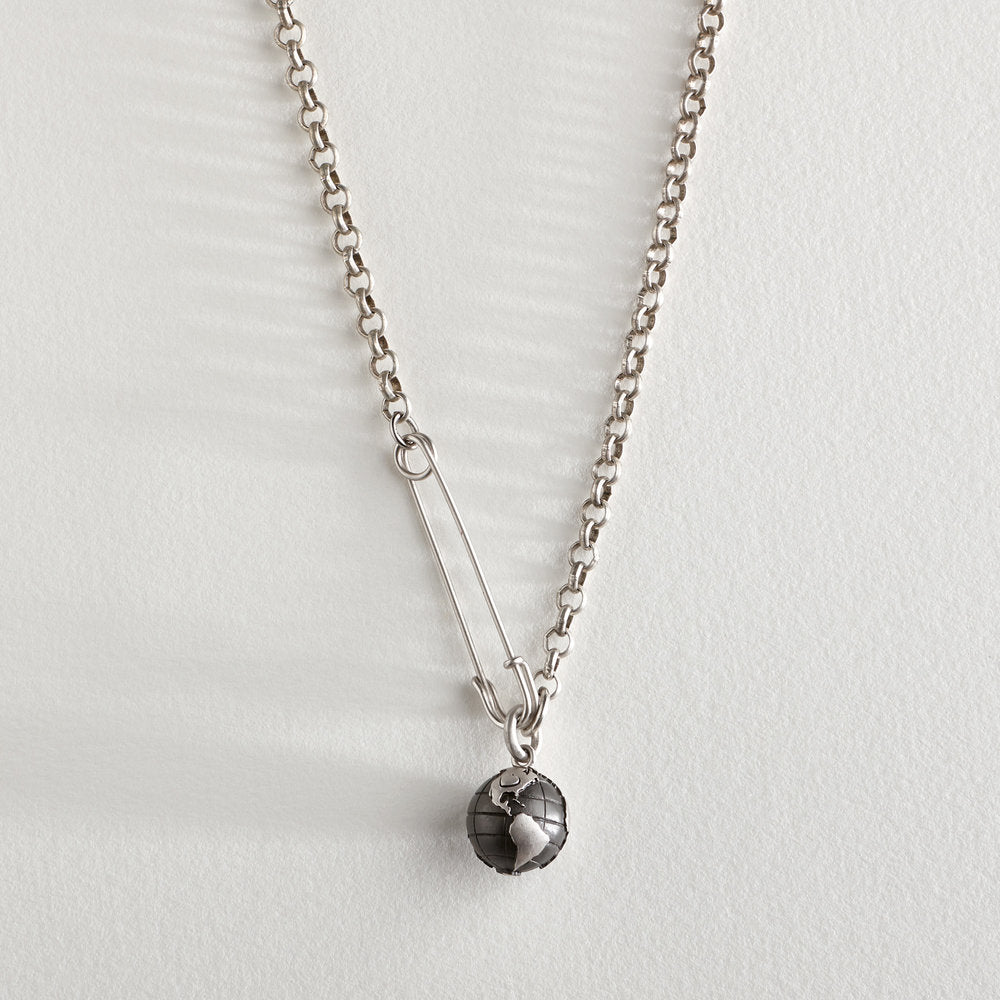 Rhodium-plated sterling silver (will not tarnish) globe charm and safety pin on base metal chain. A heart is placed on the United States symbolizing tolerance and love for all human beings. Fastens in the front.Inspired by Brexit, the Safety Pin is a symbol expressing to others whose safety may be compromised by their gender, race, religion, sexual preference, immigration status, or (dis)ability that it is safe to approach the wearer and if needed, ask for help.Length: 21""