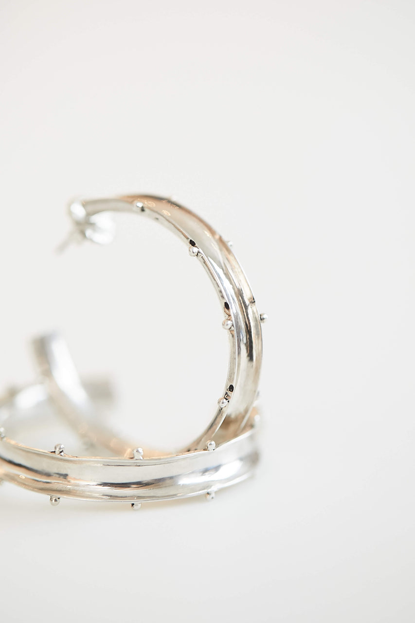 "These handcrafted hoop earrings were made by silversmiths in a small rural village in Thailand. Designed by Houser, they feature a concave shape with tiny dots accenting the edges.  1.75"" in diameter  Available in Fine Silver and Brass."