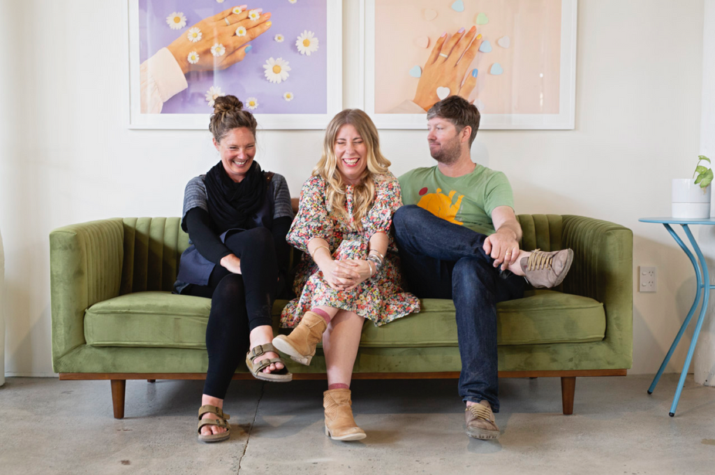 Photo of three people on a couch. Two are laughing.