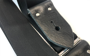 Black Guitar Strap Made From Seat Belt Material With Leather Ends