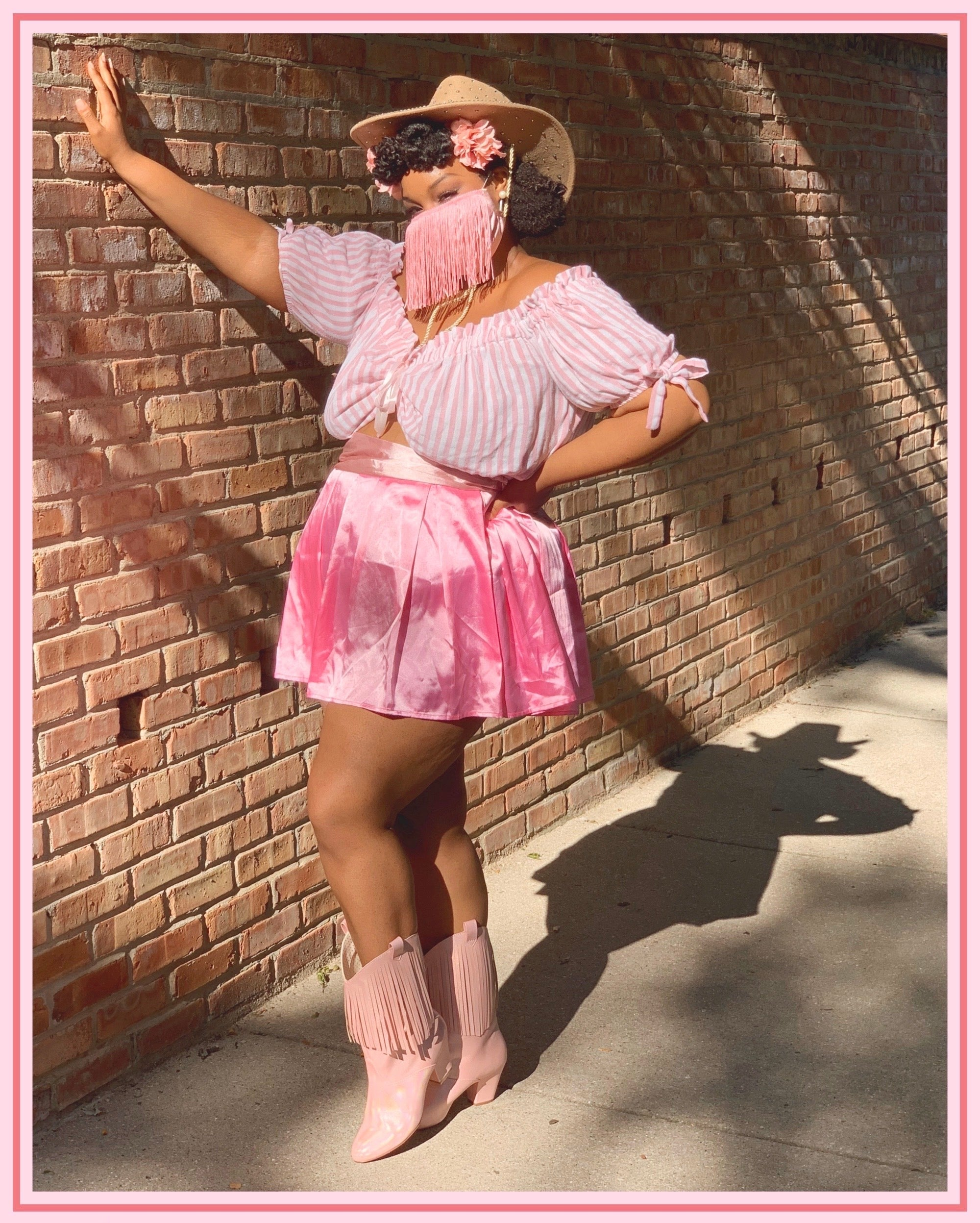 iridessence leaning her hand on a brick wall, wearing a fringe face mask, satin pink skirt with a pink striped peasant top. Standing in the Hamilton western fringe boot in pink.