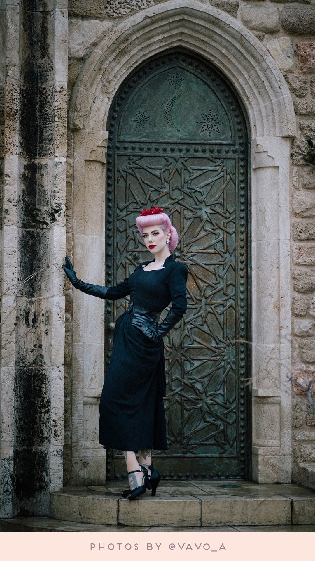 standing in front of an stone & iron doorway in all black Dafna stands balanced on one leg streamlining her figure. behind her the gothic style door towers over Dafna. with one gloved hand resting on the stone doorframe at shoulder height, Dafna stands slightly leaning back with an arm on her hip looking into the camera.  photos by @vavo_a