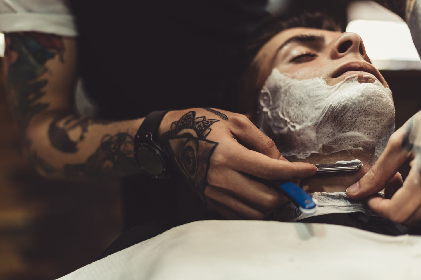 man getting straight razor shave from barber