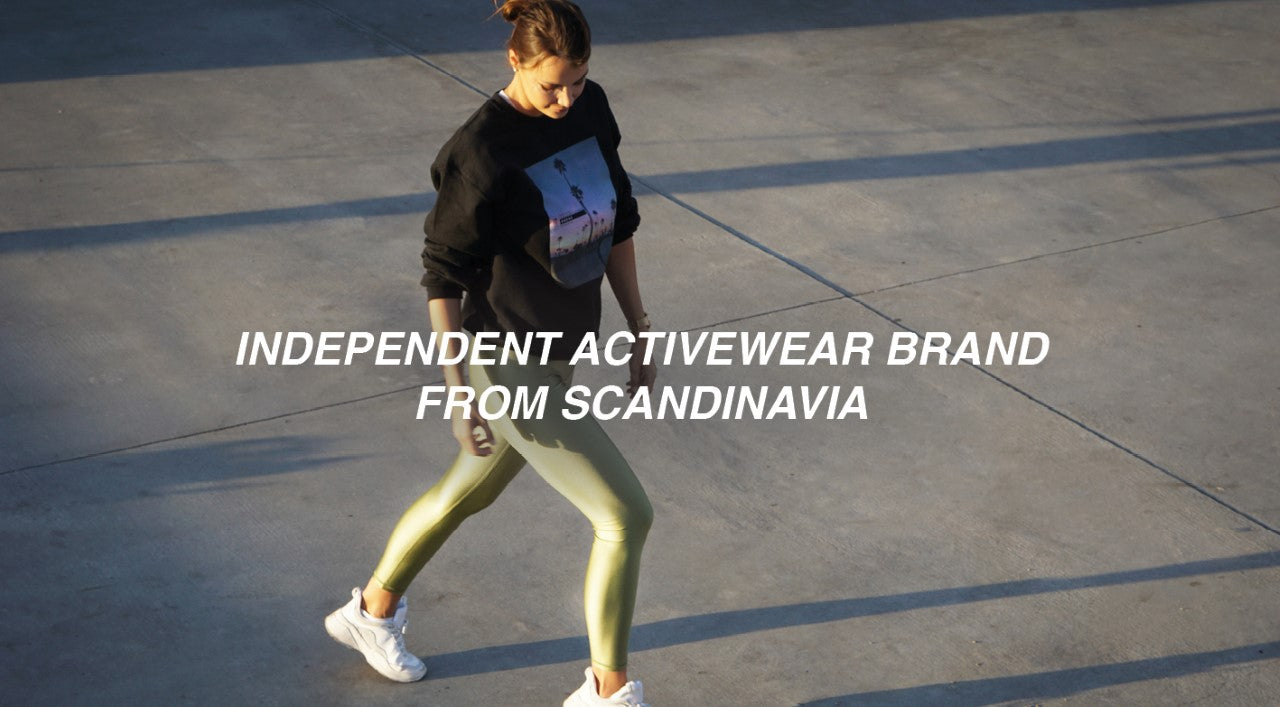 LEON NORD Activewear ethically made in small batches, woman walking with matcha green leggings and a black sweater with a picture of manhattan beach on it - the squad sweatshirt