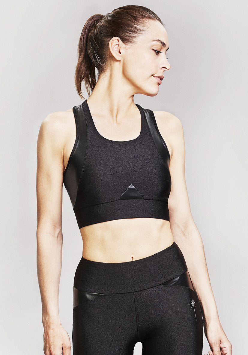 The LEON NORD Capella Crop Top / Sports bra in black is a sleek activewear statement piece with vegan leather paneling hugging and contouring the chest and shoulders