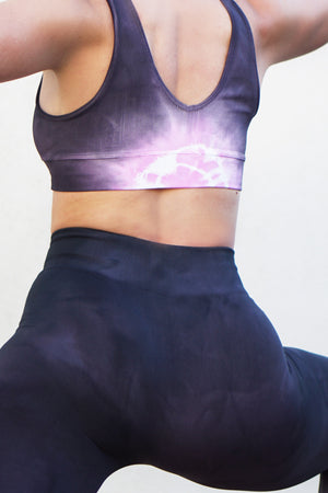 woman doing yoga pose in tie dye active wear in pink and graphite colors