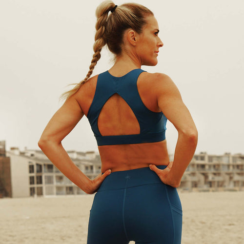 Activewear set made from recycled plastic bottles in blue, blonde woman wearing it on the beach