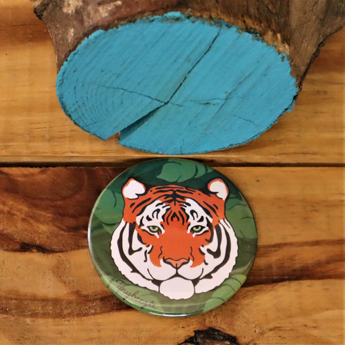 round pocket mirror with tiger illustration on green background