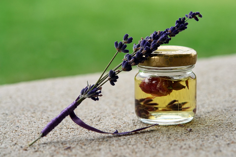 ALT Text: Lavender plant on top of an essential oil