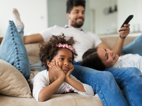 A family on the couch watching TV