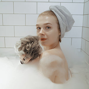 woman wearing hair wrap and holding shower pouf
