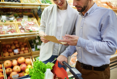 couple looking at shopping list in the produce section