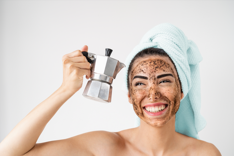 woman with coffee grounds on her face holding a moka pot