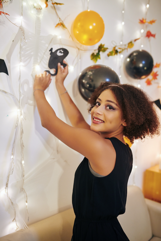 Woman putting up halloween decorations
