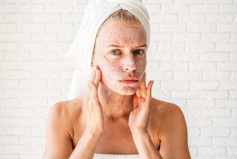 woman concerned while putting face scrub