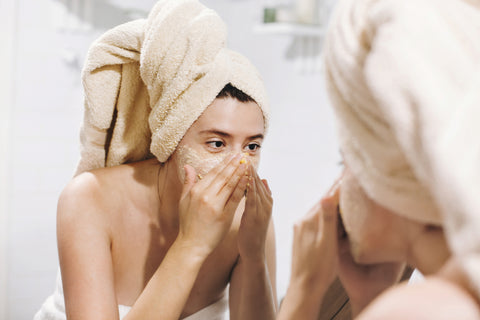 woman using face scrub while looking in the mirror