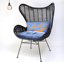copper pendant light and black rattan egg chair