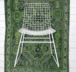 White metal wire dining chair with green rug