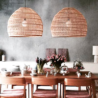 Hand woven large wicker basket pendant light above a dining table