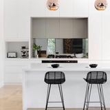 White kitchen bar with black rattan bar stools