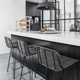 Black and white kitchen with natural black rattan bar stools in Nordic style