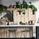 All natural wood kitchen with modern black metal wire bar stools