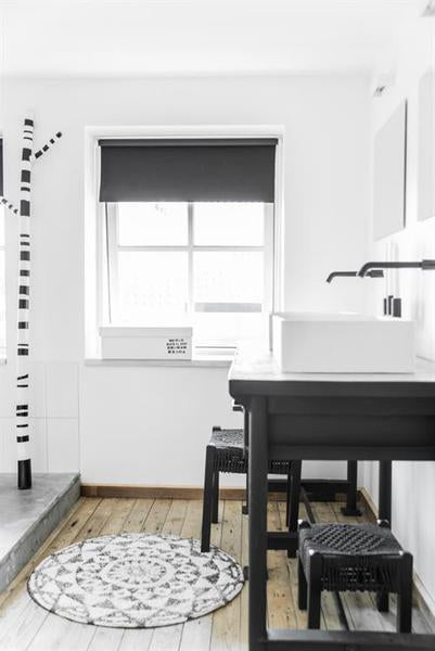 Black and white styled bathroom with medium size round bath mat