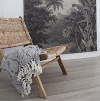 Rattan lounge chair with black white and grey diamond pattern throw blanket