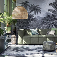 living room with green couch, rattan wicker pendent and metal side tabel